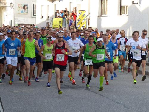 Start der vielen vielen Läufer (gekleidet mit bunten Trikots und Sportbekleidung), die gerade loslaufen.