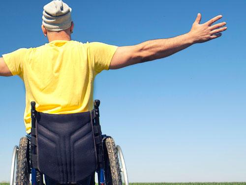Mann (Ansicht von hinten) in Rollstuhl mit ausgebreiteten Händen bei strahlend blauem Himmel.