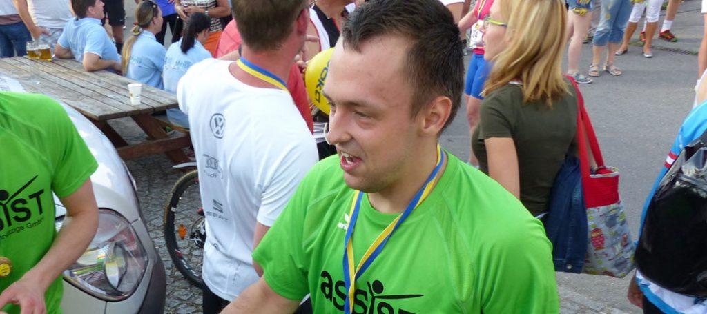ASSIST-Läufer (Sieger) mit ASSIST-Sport-T-Shirt nach einem Lauf mit Medaille umgehängt!