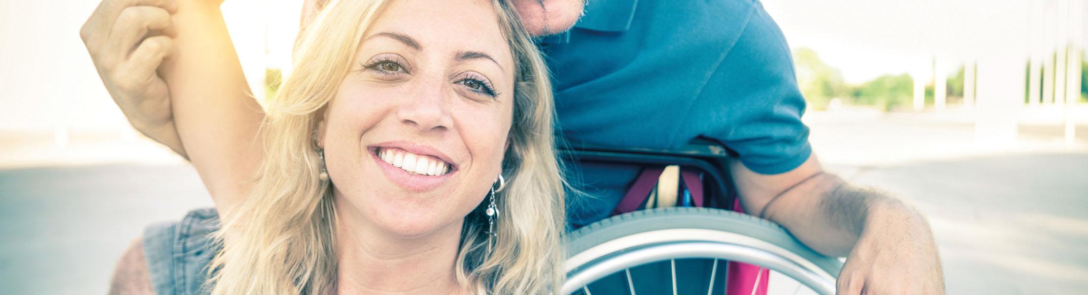 Mann im Rollstuhl und Frau, die ihn begleitet (Symbolfoto für Projekt ASSISTMOBI)