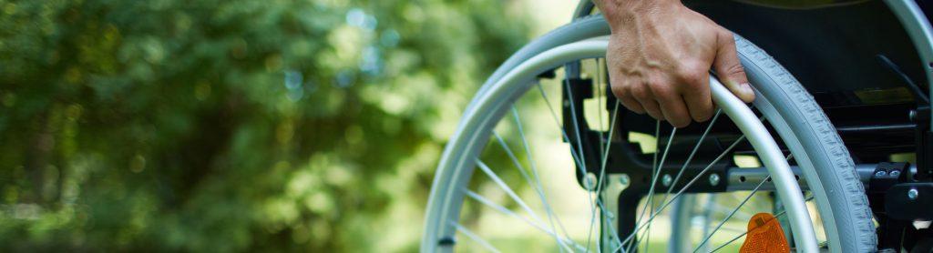 Rollstuhl-Rad (mit Hand, die gerade anschiebt) im Park.