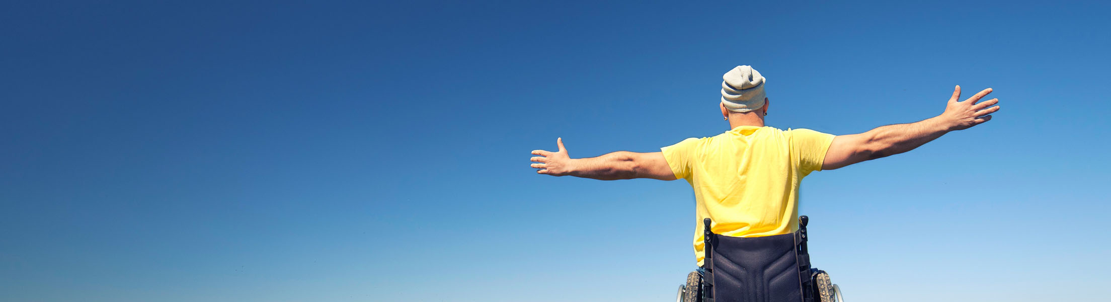 Mann im Rollstuhl (Ansicht von Rückseite) mit ausgestreckten Armen an Tag mit strahlend blauem Himmel.