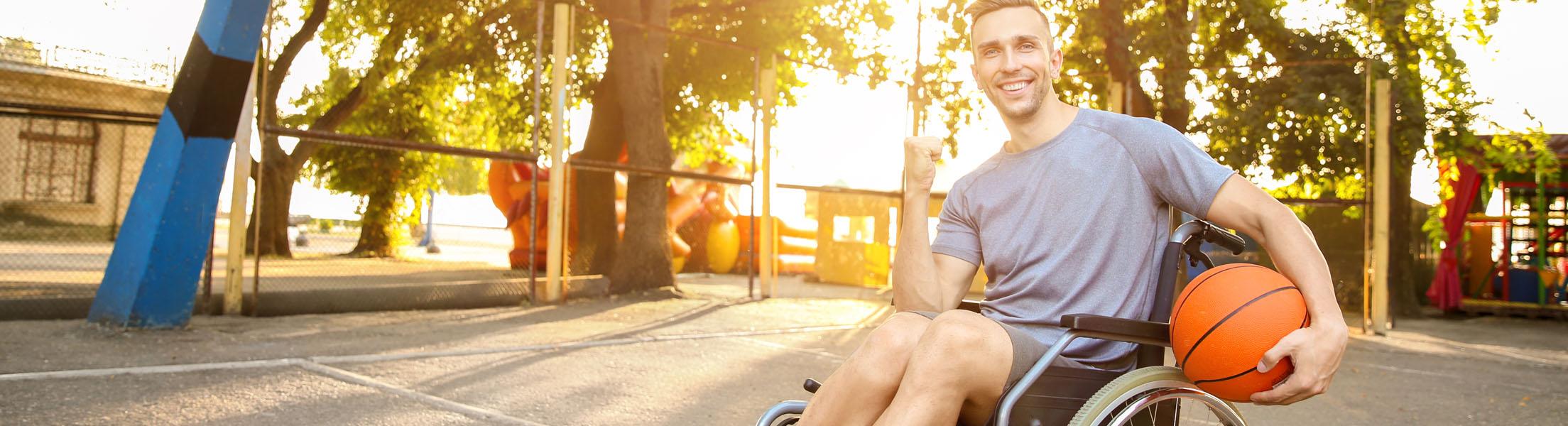 Junger Mann im Rollstuhl mit Basketball in der Hand auf Basketball-Platz im Sonnenschein.