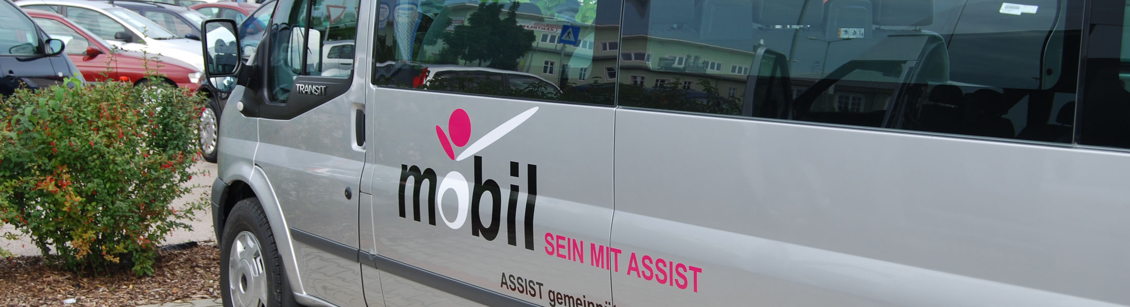 """ASSIST-Bus von der Seite abgebildet mit dem Logo """"mobil sein mit ASSIST"""" darauf."""