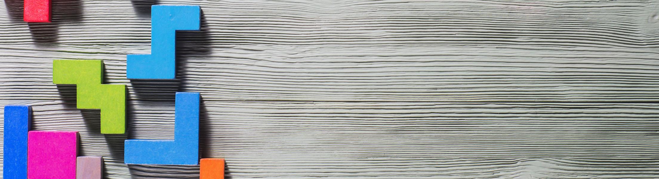 Holztafel: Darauf befinden sich bunte Steine aus Holz, die alle unterschiedliche Formen und Farben haben (Symbol für das Bausteinsystem bei ASSIST).