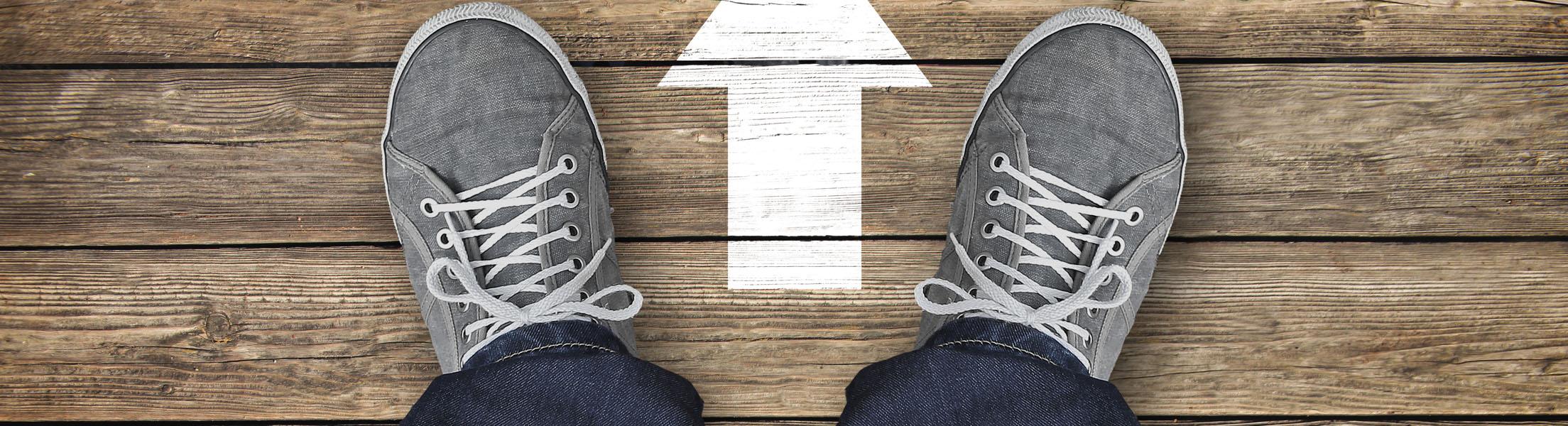 2 Füße in grauen Turnschuhen, die auf Holzboden stehen. Vor ihnen ein Pfeil Richtung Zukunft.