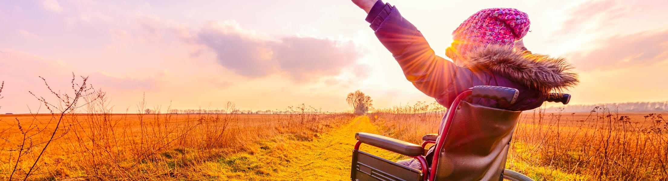 Junge Frau im Rollstuhl (Ansicht von der Seite), die am Feld stehend Richtung Sonne blickt.