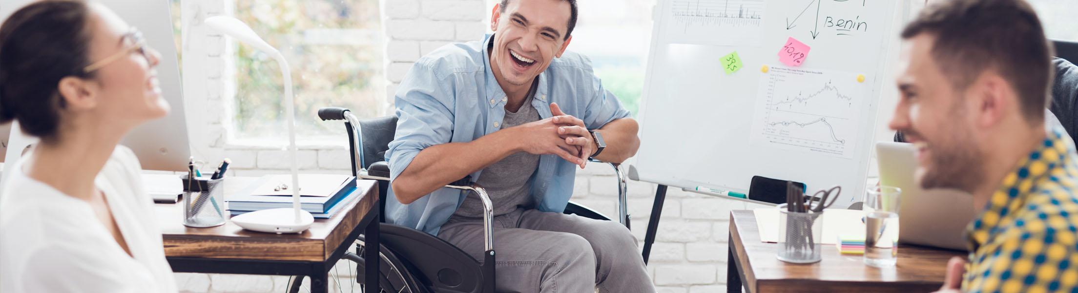 2 Männer (einer davon im Rollstuhl) und eine Frau unterhalten sich lachend im Büro.