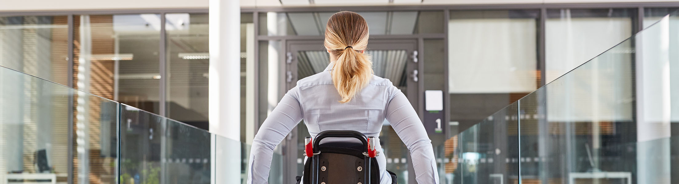 Frau im Rollstuhl (Ansicht von hinten) fährt in einem Bürogebäude einen Gang entlang mit Glas-Geländer.