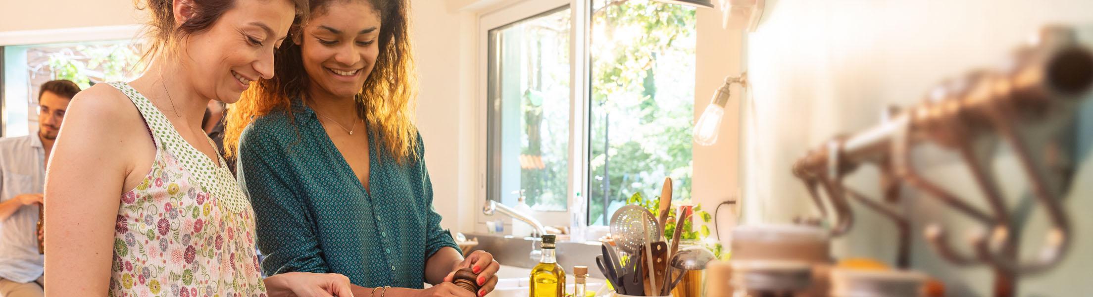 2 Frauen kochen gemeinsam in der WG-Küche.