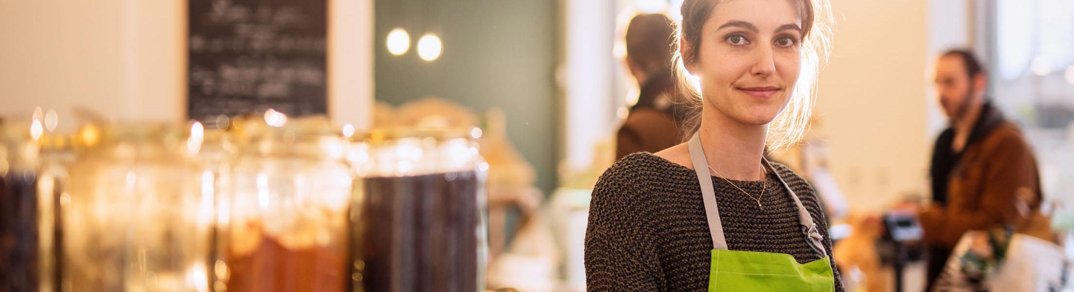 Junge Frau mit Schürze arbeitet in Unverpackt-Laden und verkauft Lebensmittel aus Gläsern.