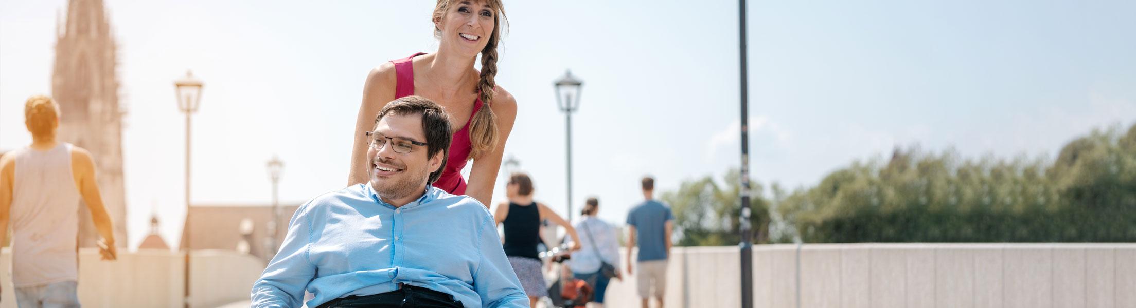Junge Dame begleitet Herren im Rohlstuhl in der Stadt beim Spaziergang.