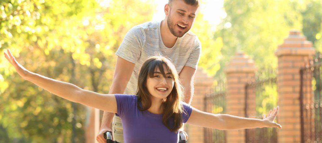 Eine junge Frau im Rollstuhl wird von einem Begleiter durch den Park geschoben; beide lachen voll dabei; Frau im Rolli hat ihr Arme weit von sich gestreckt (wie wenn sie fliegen würde).