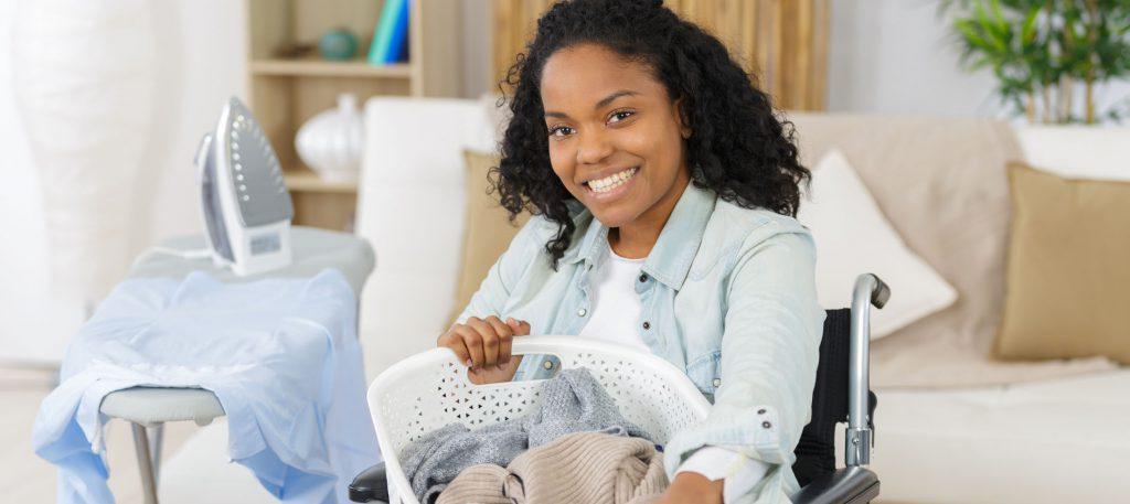 1 junge Frau im Rollstuhl macht gerade ihre Wäsche (Bügelbrett, Bügeleisen, Wäschekorb).