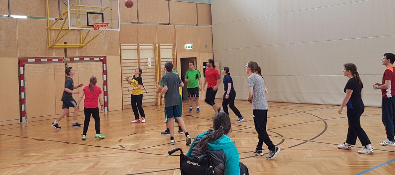 Gruppe von Kund*innen und Mitarbeiter*innen bei Basketballspiel im Turnsaal