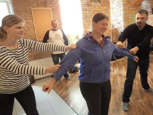 Die beiden Vortragenden halten die Person in der Mitte jeweils mit beiden Händen an den Ärmeln der Kleidung fest, um zu demonstrieren, wie man eine Person festhält, um präventiv  weitere Gewalt zu vermeidet (Foto zu Part-Konzept)