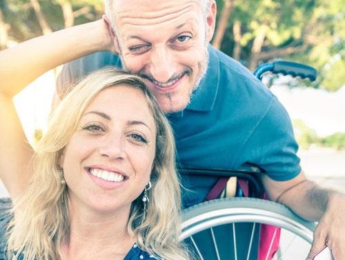 Mann im Rollstuhl und Frau, die ihn umarmt (als Symbolbild für ASSISTMOBI)
