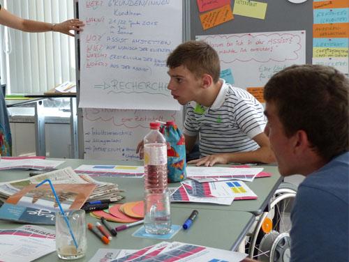 2 Kunden sitzen am Tisch voller Unterlagen und Zeitungsschnipsel bei einem Seminar
