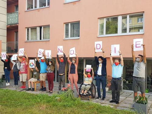 """Darsteller-Gruppe hält Schilder in den Händen mit den Worten """"Wir sind die ..."""""""