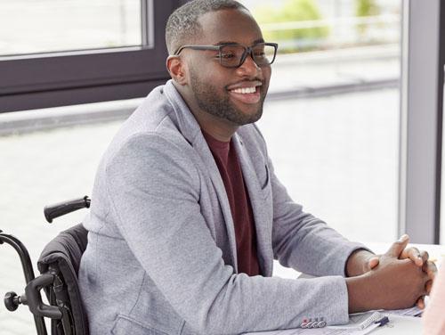 Junger Mann im Rollstuhl bei Kennenlern-Gespräch