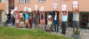 """Darstellergruppe zeigt Schilder mit der Aufschrift """"Wir sind die ..."""""""