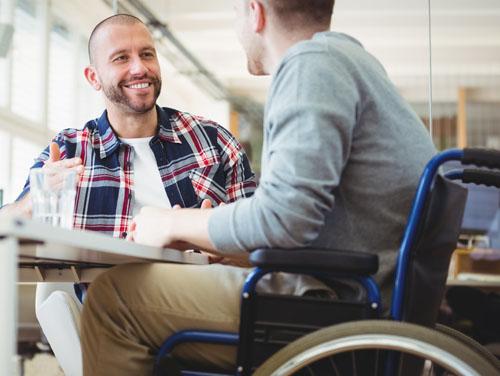 2 Männer (einer davon im Rollstuhl) sitzen gemeinsam am Tisch und sprechen miteinander.