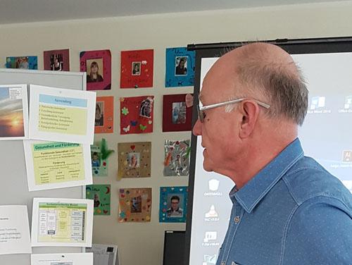 Hr. Greier steht an der Pinwand und erklärt anhand von Bilderrn die Inhalte der Weiterbilldung.