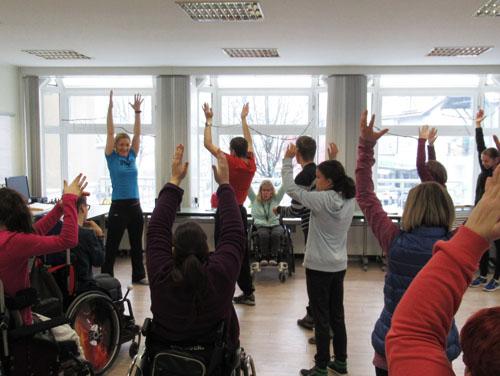 Eine Gruppe von Personen in der ASSIST Amstetten macht gerade im Gruppenraum Bewegungsprogramm (alle stehen mit erhobenen Händen im Raum).