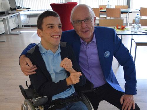 Hr. Greier mit einem Kunden aus Amstetten (Rollstuhlfahrer) lachen am Tag der offenen Tür gemeinsam in die Kamera.