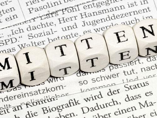 """Ein Zeitungsausschnitt mit vielen Worten, darauf liegend  6 Holzwürfel mit der Aufschrift """"mitten"""" (von mittendrin.)"""