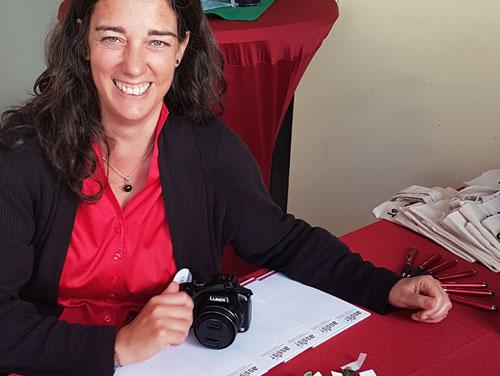 Frau von Hodenberg sitzt am Infotisch mit Infomaterialien über die ASSIST (Blöcke und Kugelschreiber) und hält eine Kamera in der Hand.