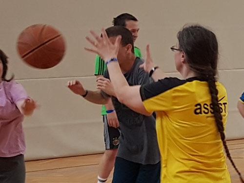 Mehrere Personen im Turnsaal beim Basketballspiel: Der Ball fliegt gerade durch den Saal.
