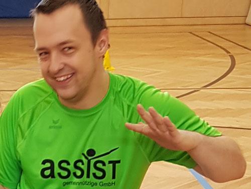 Portrait eines Kunden mit einem Sport-T-Shirt, wo ASSIST draufsteht im Turnsaal.