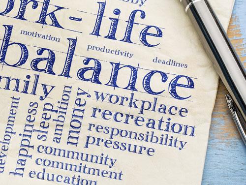 """Symbolbild: Blatt Papier mit vielen englischen Worten darauf, wie """"work-life-balance, workplace, usw."""" und Kugelschreiber"""