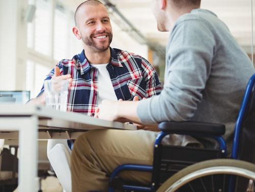 2 Männer (einer davon im Rollstuhl) sitzten an Tisch und unterhalten sich miteinander.