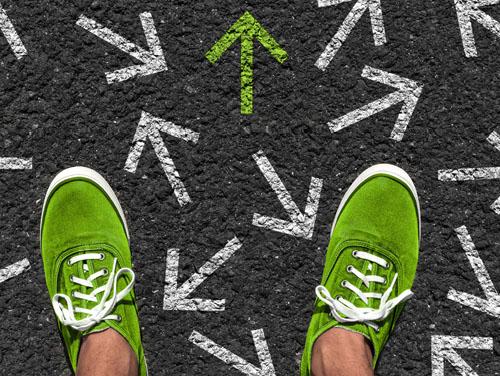 2 Füße in grünen Turnschuhen stehen auf der Straße. Unter ihnen viele Pfeile in verschiedenen Richtungen, die eingeschlagen werden können (Symbolbild für Berufsorientierung).