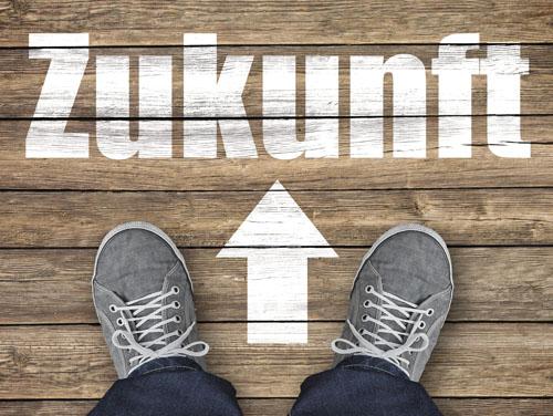 """2 Füße mit grauen Turnschuhen stehen auf einem Holzboden vor einem weissen Pfeil, der auf das Wort """"Zukunft"""" zeigt."""