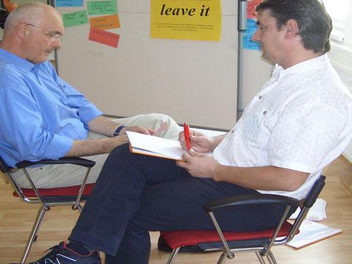 Vortragender und Teilnehmer sitzen sich auf 2 Stühlen gegenüber mit Stift und Papier in der Hand und sprechen miteinander.