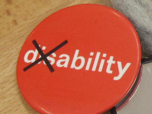 """Roter Button mit der Aufschrift """"disability"""", wobei """"dis"""" durchgestrichen ist, damit das Wort """"ability"""" (Möglichkeit) stehen bleibt."""