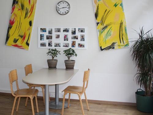 Ein Willkommenstisch mit 3 Stühlen, Blumentöpfe und bunte Fotos und Bilder an der Wand - der Eingangsbereich des Teilbetreut Wohnen Stützpunktes in der Sturzgasse.