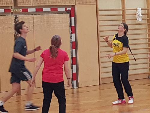 3 Personen im Turnsaal spielen Basketball.