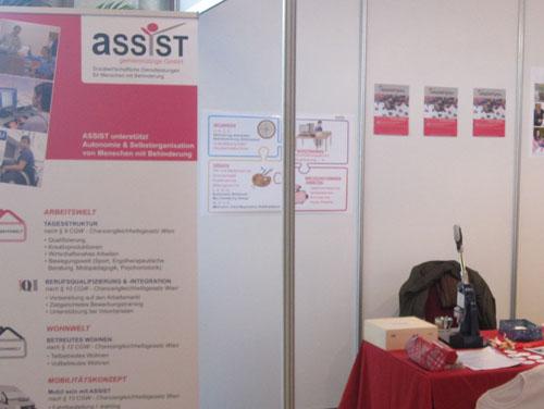 Ausschnitt eines Messestandes mit ASSIST-Plakaten, Aufsteller und einem Tisch mit einer Buttonsmaschine darauf.
