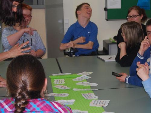 Eine Gruppe von Seminarteilnehmer*innen und 2 Vortragenden sitzt gemeinsam an einem Tisch und arbeitet mit Kärtchen zum Thema Persönliche Zukunftsplanung.
