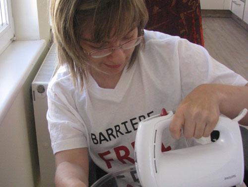 """Eine junge Dame (Kundin) trägt ein ASSIST-T-Shirt mit der Aufschrift """"Barrierefrei sein"""" und hält einen Küchen-Handmixer in der Hand, mit dem sie gerade Kuchen macht."""