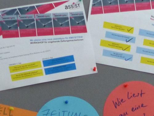 Seminarunterlagen auf der Pinnwand: Man sieht Zeitungscovers der ASSIST und liest Workshop-Infos und Stichworte dazu.