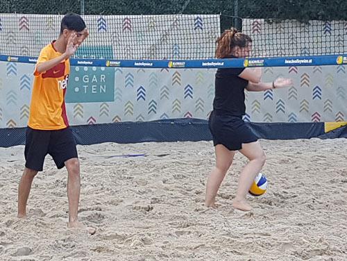 2 Personen am Beachvolleyballfeld (Sandboden und Netz)  auf der Jagd nach dem Ball.