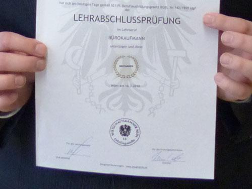 Zertifikat der bestandenen Lehrabschlussprüfung für Bürokaufleute (von 2 Händen gehalten).