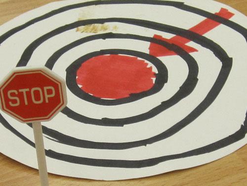 Gezeichnete Zielscheibe mit rotem Punkt in der Mitte und rotem Pfeil, der auf die Mitte zeigt; 1 Stopptafel in der linken Ecke davor verweist auf mögliche Hindernisse in der Zielgeraden. Ein Smybolbild für Persönliche Zukunftsplanung