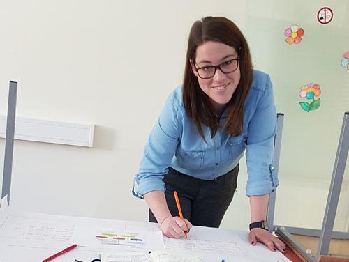 Frau Leberzipf steht an Schreibtisch und füllt gerade Unterlagen vor sich auf dem Tisch aus.