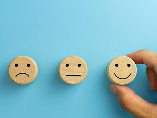 3 Smileys zeigen mürrisches, neutrales und lachendes Gesicht; 1 Hand greift nach dem lachenden Smiley.